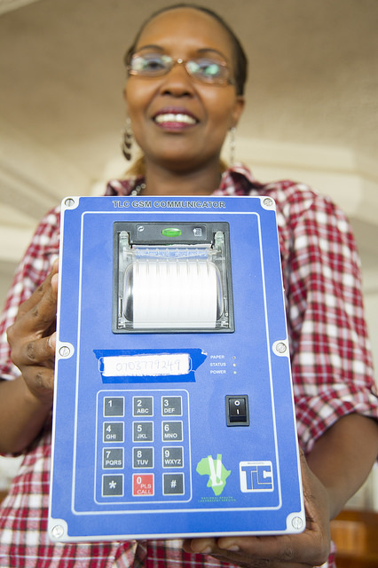 Dr. Cathy Mwangi, head of the CDC Foundation-funded MPEP initiative, poses with an SMS printer